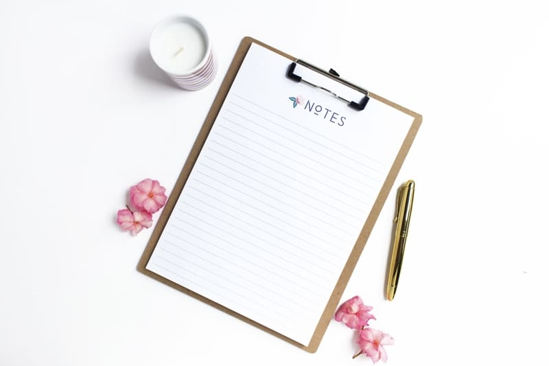 Lined Sheet Of Paper Titled Notes On A Clipboard With Pink Flowers A Gold Pen And A White Candle