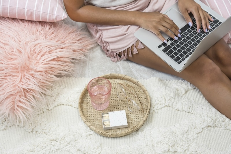 Woman Sitting On White Bedding With Laptop And Pink Pillows