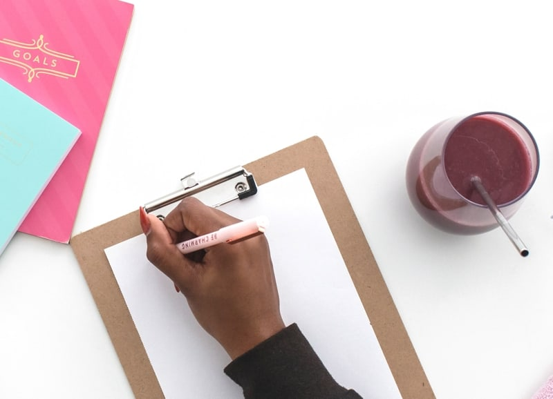 Woman Writing On Paper Against Clipboard With Smoothie Drink And Bright Colored Notebooks