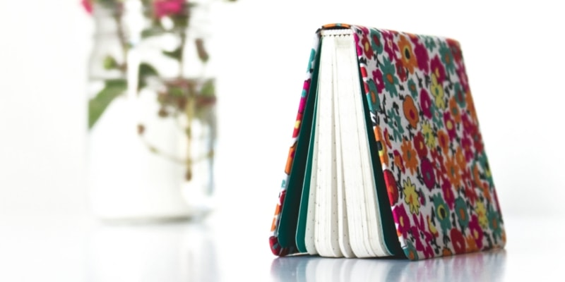 Shortpixel Plugin Header Image Of Pink And Multicolored Notebook Standing In A Tent Shape With Glass Vase Of Flowers Behind It