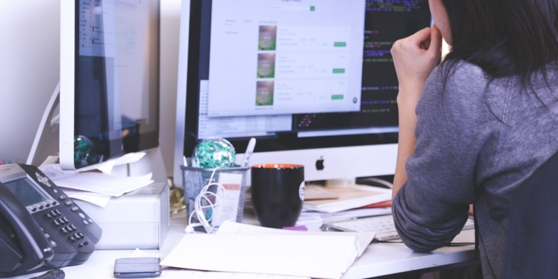 Girl Using Multiple Apple Macs At Office Desk With Mug Telephone And Other Office Supplies