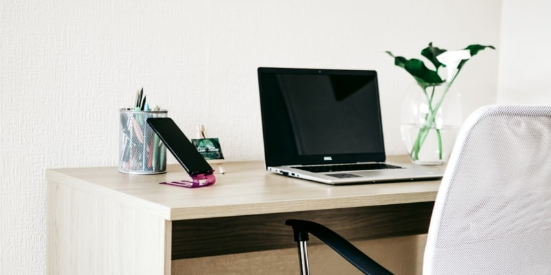 White And Light Office Area With Laptop Pot Of Pens And A Plant On A Desk With A White Chair