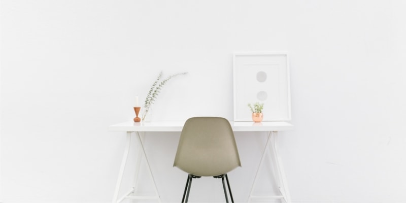 White Minimalist Desk With Coffee Colored Chair Against A White Wall