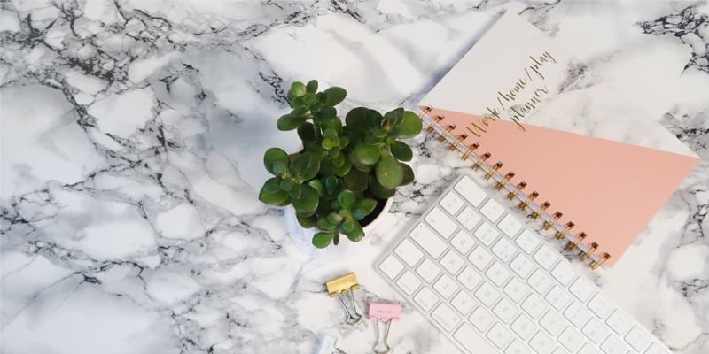 Mac Keyboard With Paper Clips Pink Notebook And Plant On Marble Surface