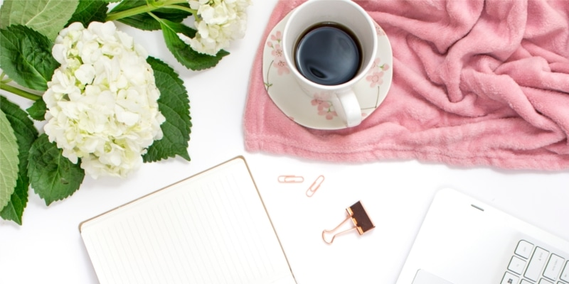 White Laptop With Flowery Tea Cup Pink Cloth Paper Clips And White Flowers