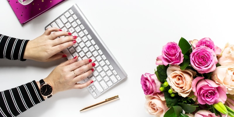 Woman Using Keyboard With Plum Purple Notebook And Arrangement Of Peach And Pink Roses