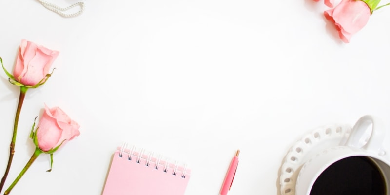 Pink Notepad Pen And Coffee Ready For Blogging With Pink Roses Scattered Around