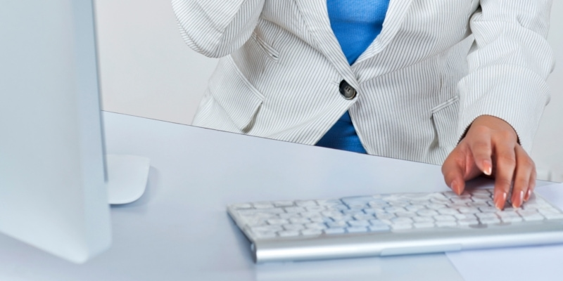 Female blogger wearing white suit using silver keyboard, white mouse & monitor