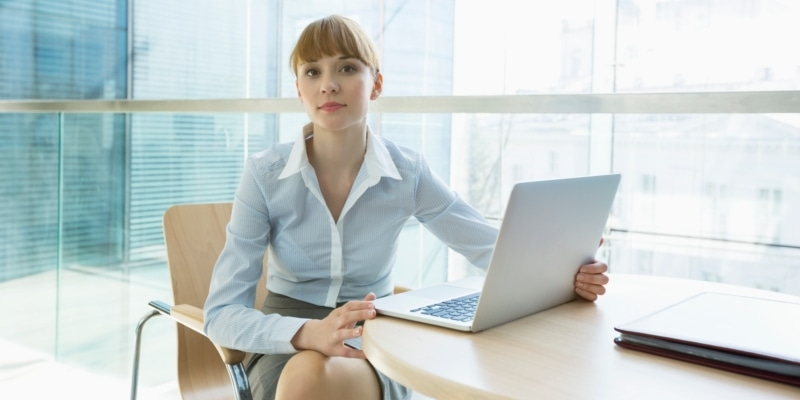 Female Blogger Using Laptop On Desk In An Office