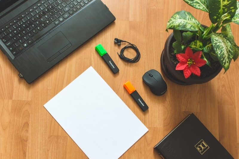 Blogging Office Desk With Black Laptop Notebook And Stationary With Red Potted Flower 1