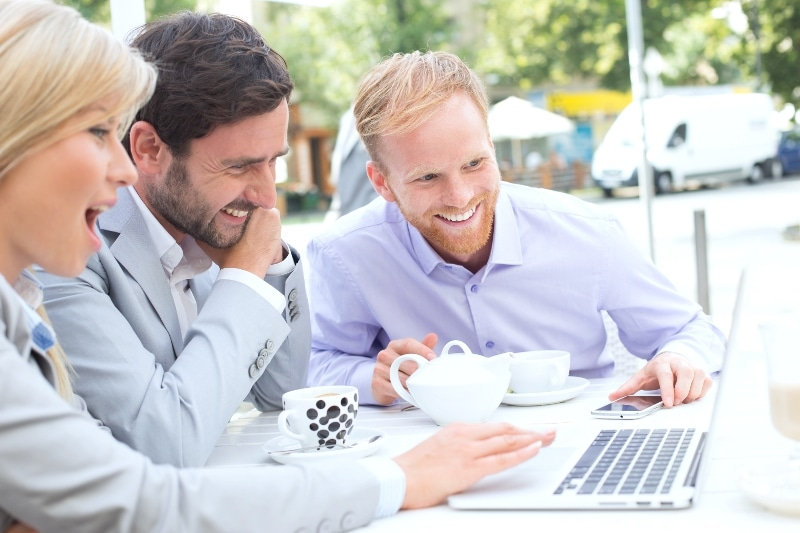 Entrepreneur Bloggers Smiling While Using Laptop And Drinking Coffee Outside 1