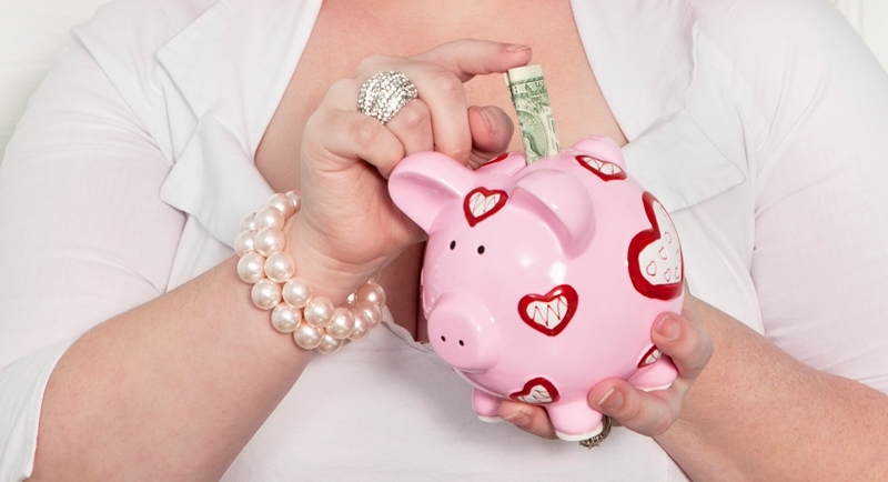 Female Blogger Making Money Blogging And Putting It Into Her Pink Piggy Bank