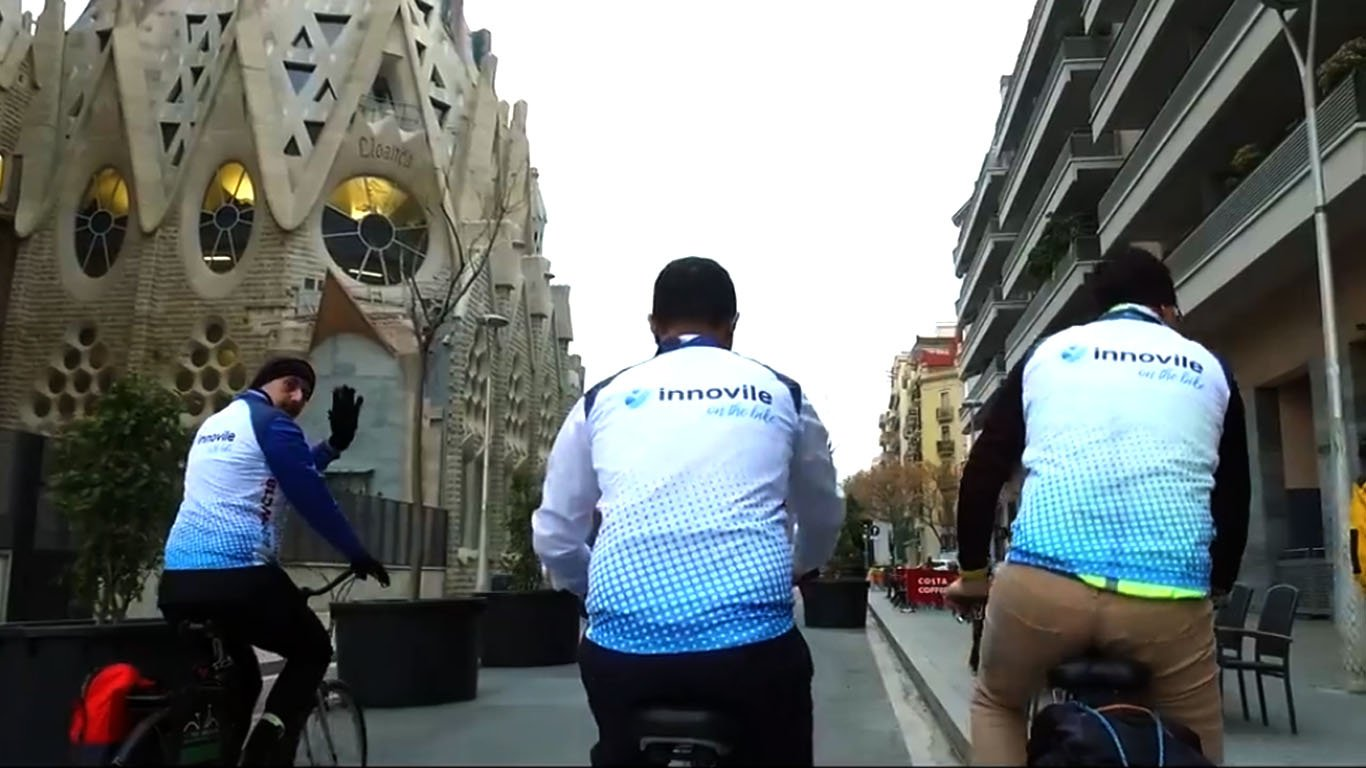 3 members of Innovile team riding bicycles in Barcelona streets