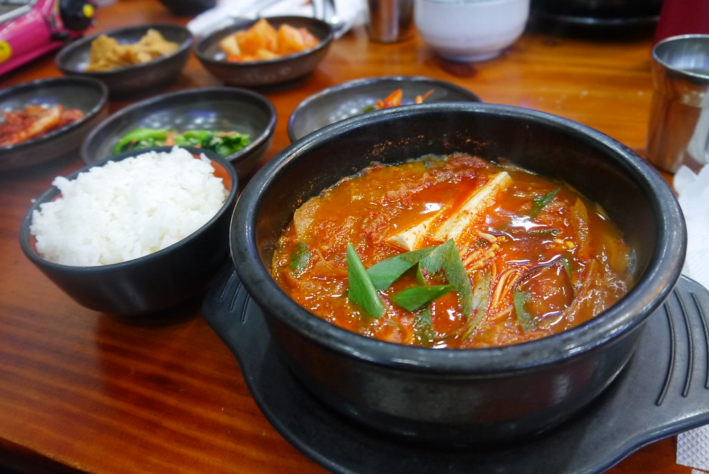 Kimchi Jjigae - A popular Korean dish that is like a stew with kimchi, rice, and side dishes.