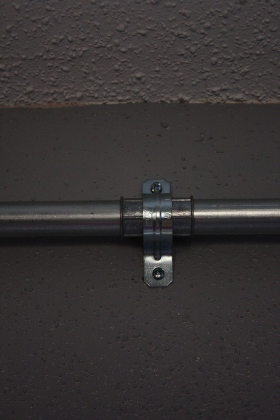 close up of two hole strap holding curtain rod to wall