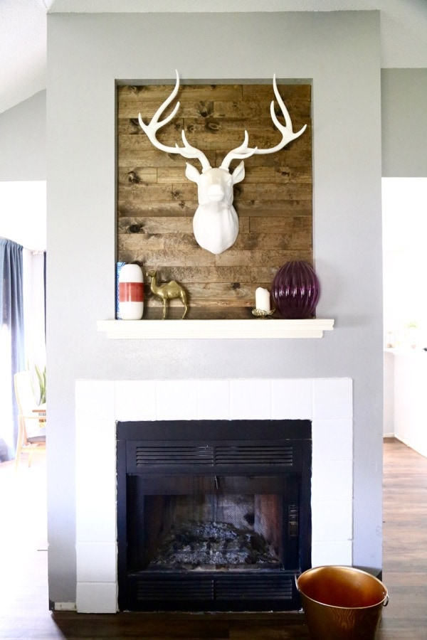 This wood-paneled fireplace was created with scrap wood in under an hour! The transformation is incredible, and this project is so easy! You can use this tutorial to make a plank wall anywhere you want!