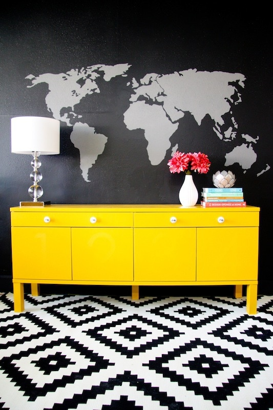 a yellow sideboard against a black wall with a map mural painted on the wall
