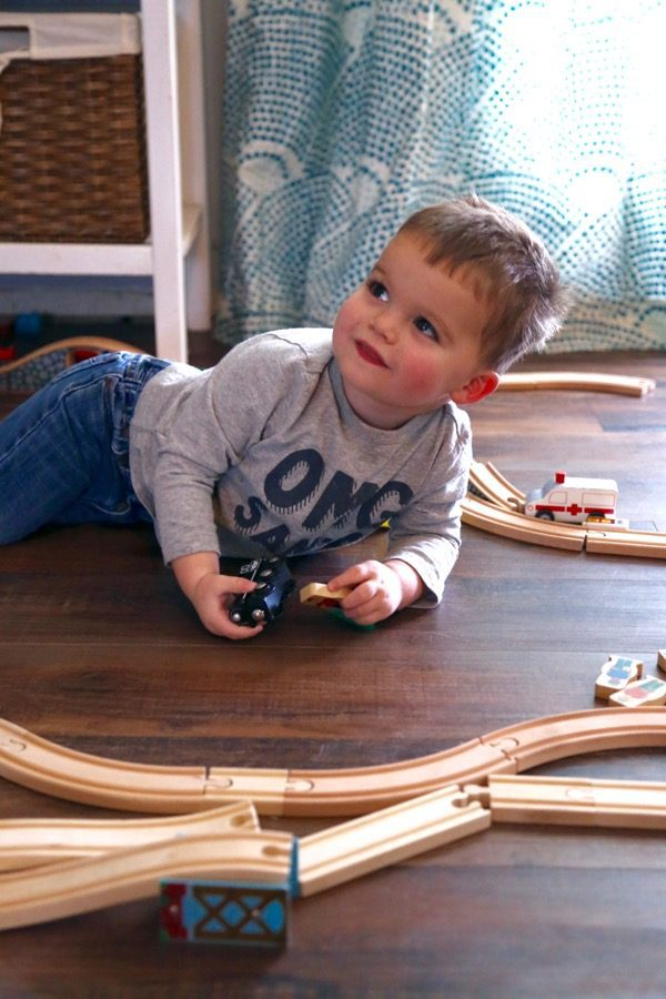 A small boy laying on the floor playing with trains