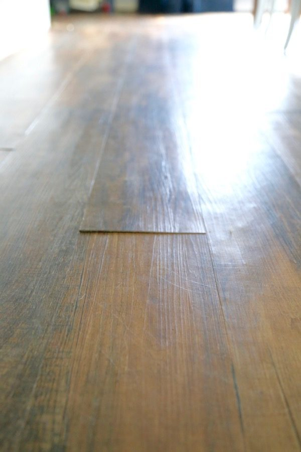 A close up of a piece of vinyl plank flooring that is peeling up off the ground