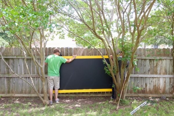 man hanging outdoor chalkboard on a fence