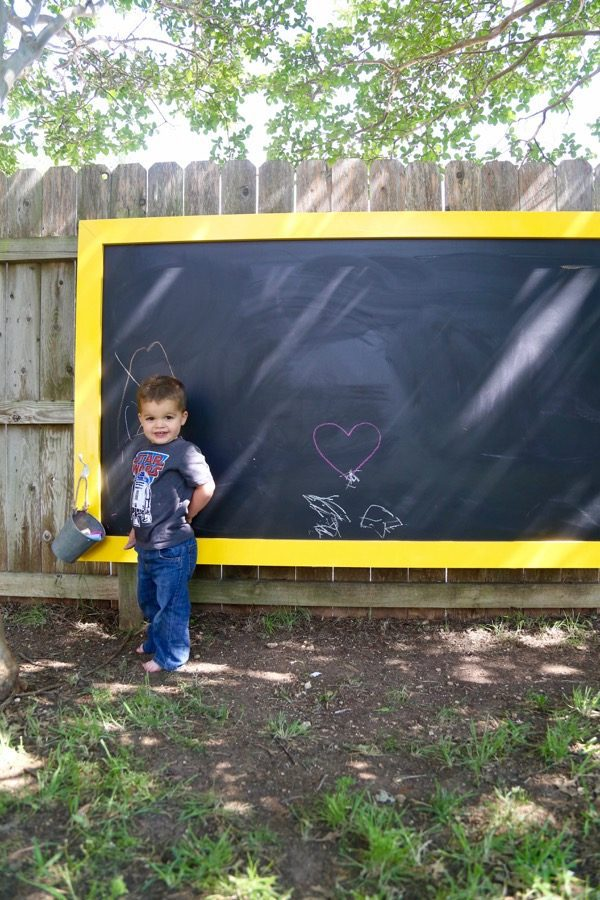 toddler posing in front of an outdoor chalkboard hanging on fence