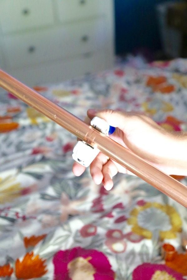 woman's hand using a pipe cutter to cut a copper pipe