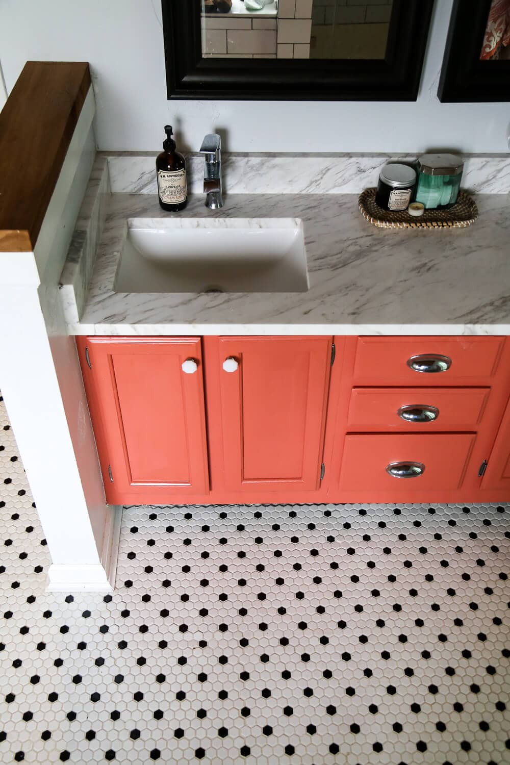 Overhead shot of master bathroom remodel - black and white hex tile, coral vanity, and quartz countertop