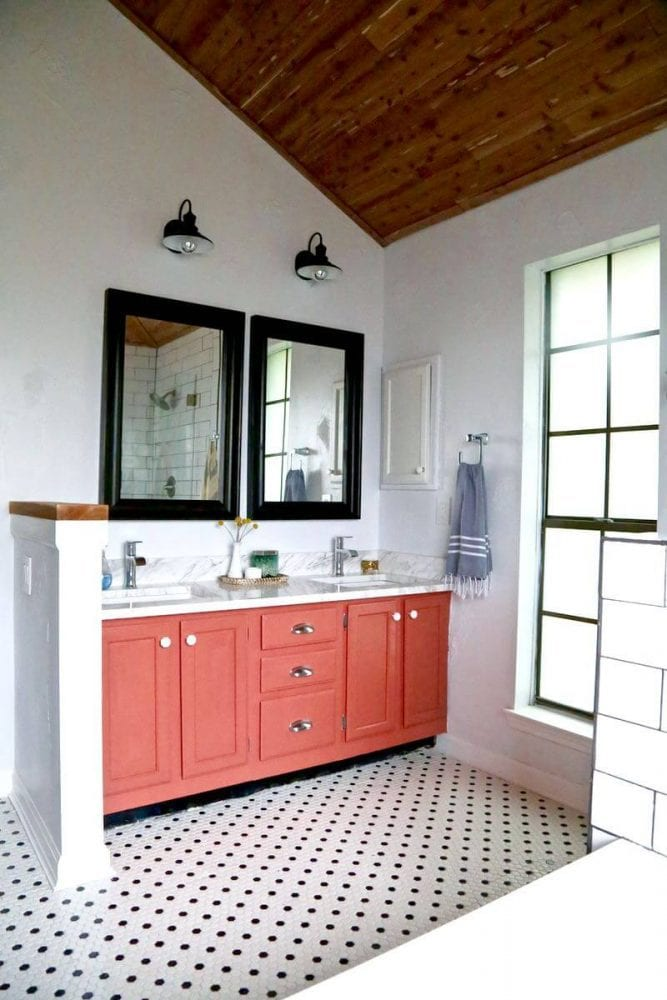 a black and white bathroom with a pink vanity