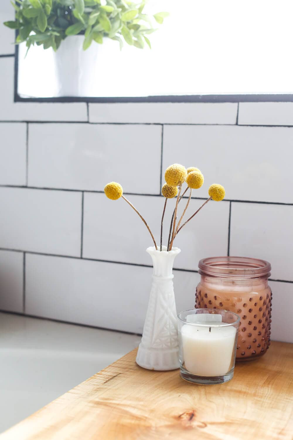 candles and flowers on top of bathtub tray