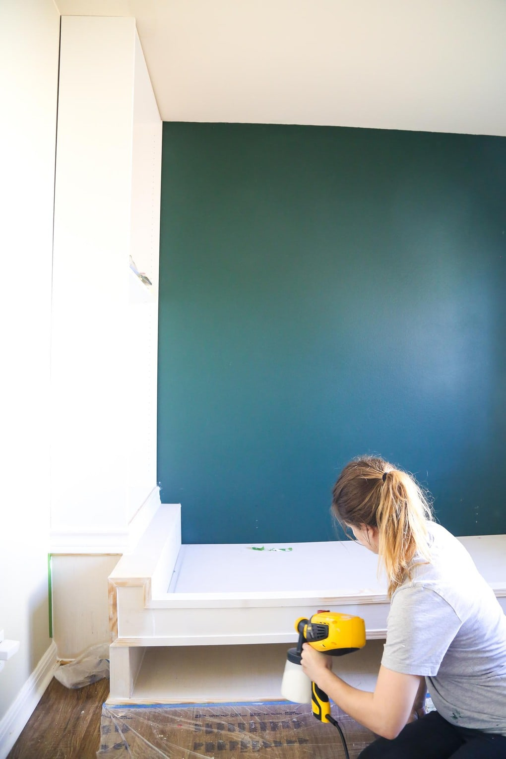 Woman using paint sprayer to paint DIY build in shelves