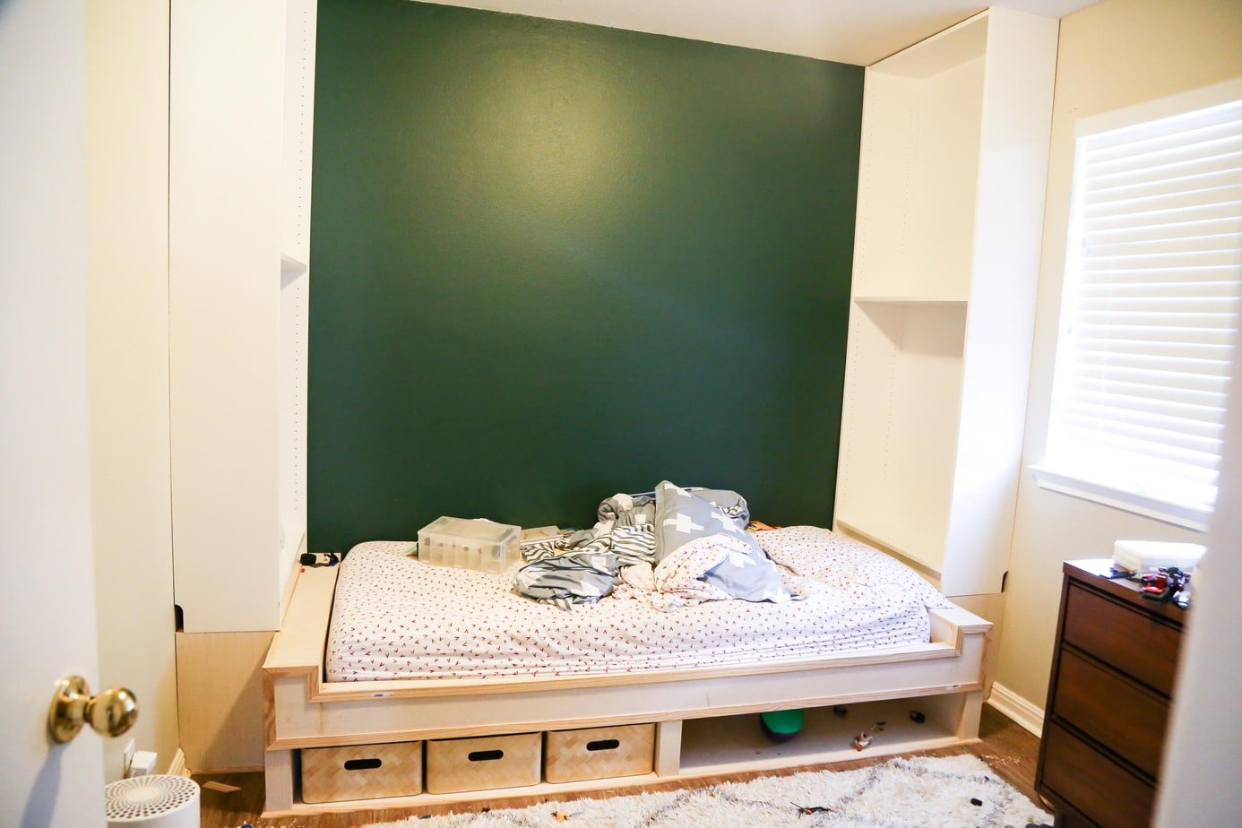 Unpainted DIY built in shelves and bed