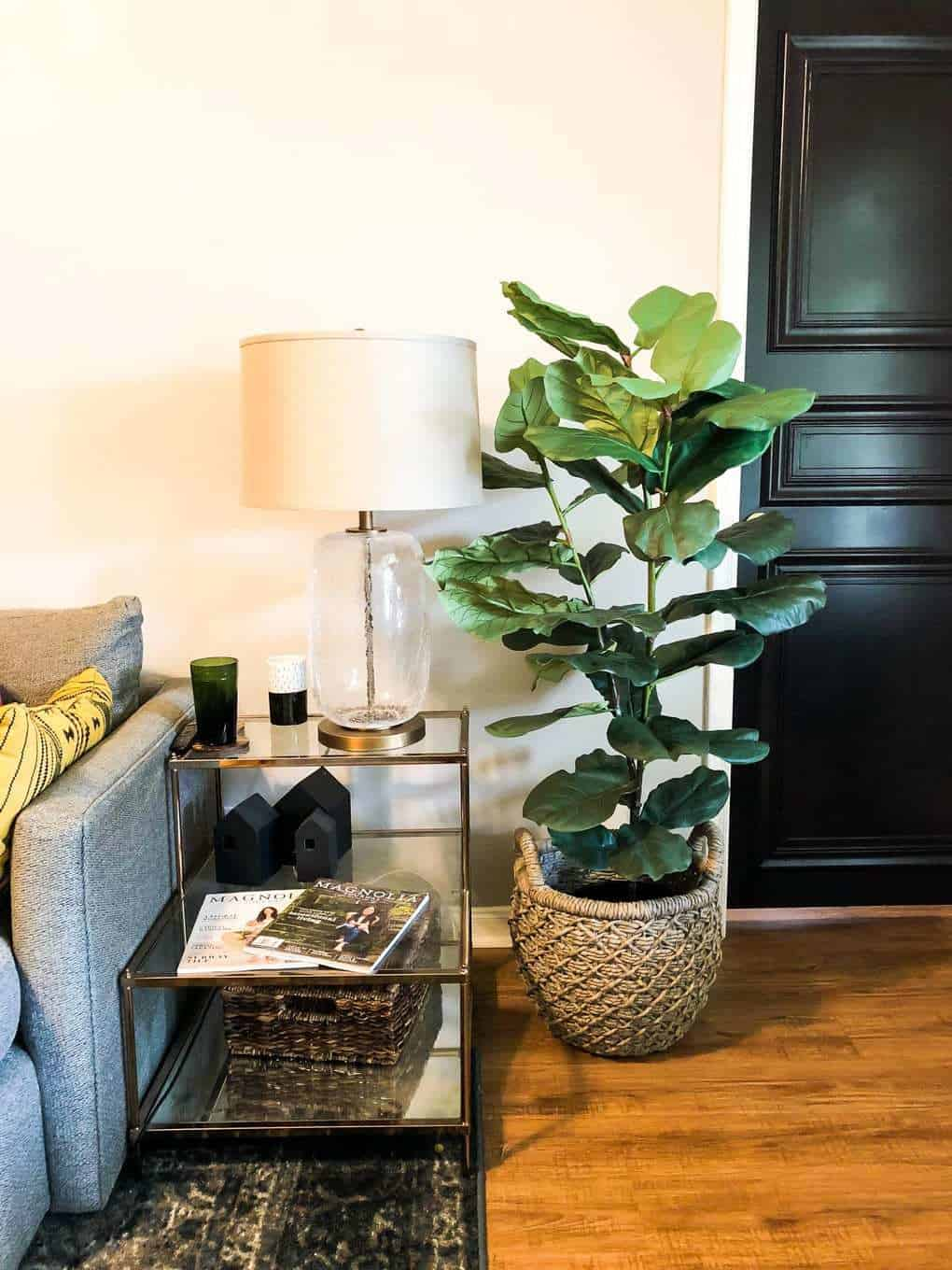 A faux fiddle leaf fig sitting next to a couch and side table