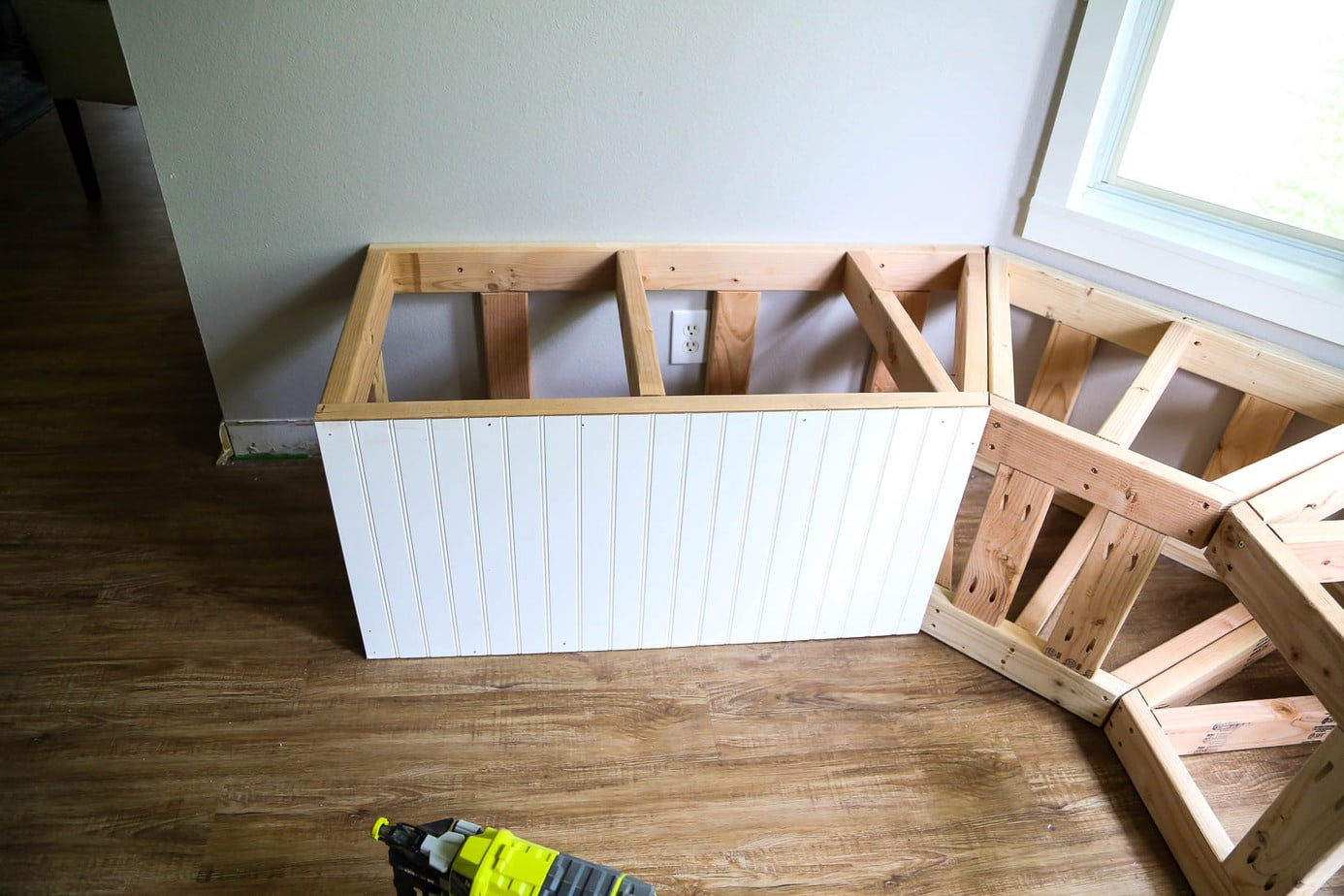 Framing for bay window bench with beadboard being installed on the front
