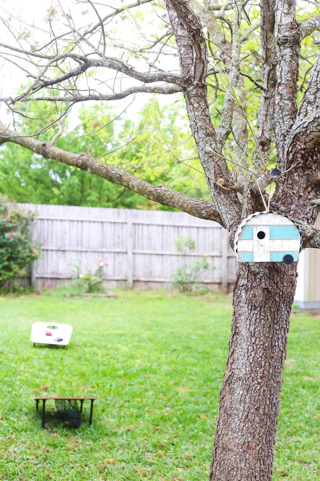 Tree with camper-shaped bird house and backyard games in the background