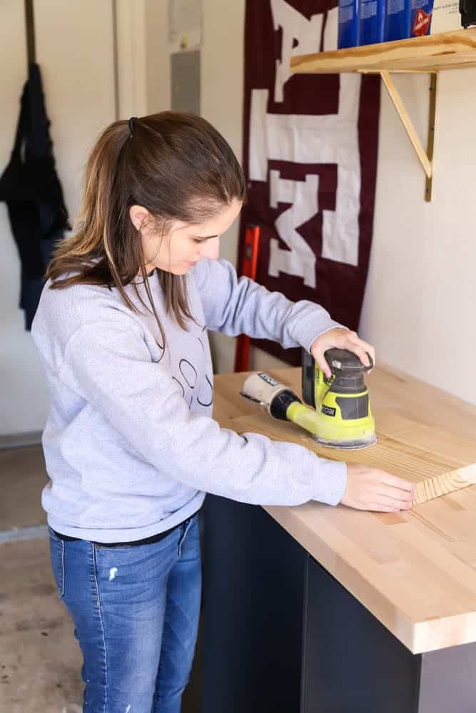 woman sanding on a work bench