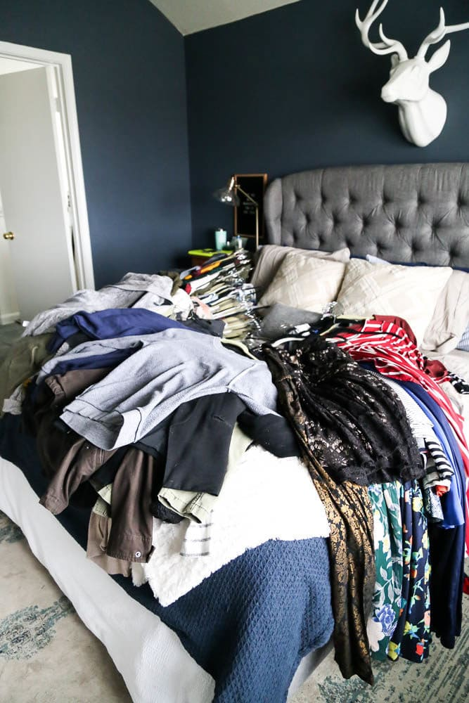 clothes laying on bed - ready to be organized