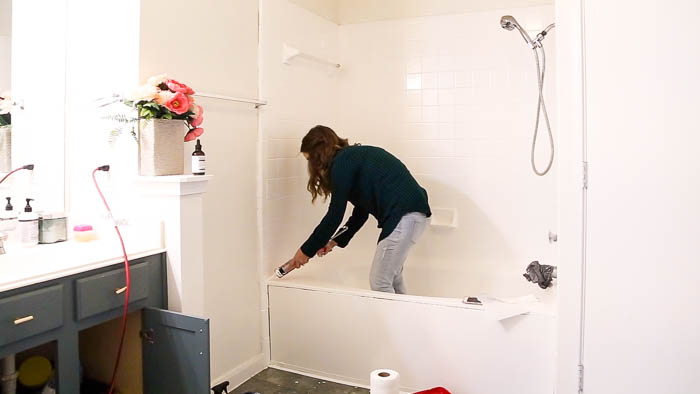 woman caulking a bathtub after painting it