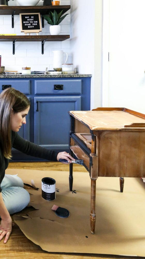 woman painting a small side table using Rustoleum Milk Paint Finish