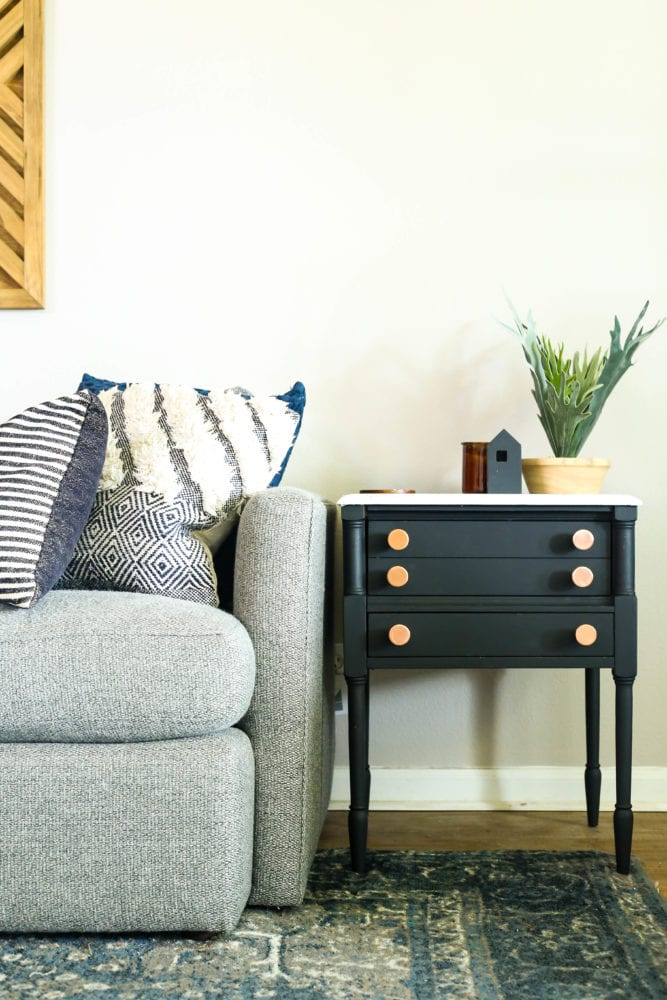 black side table with faux marble top sitting next to a gray couch