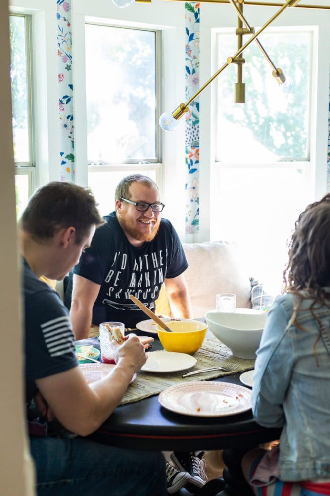 three people gathered around a table eating a meal