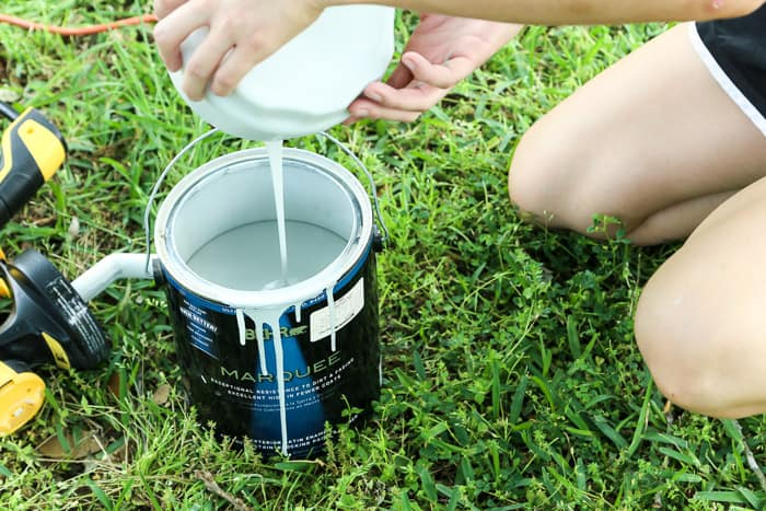 pouring leftover paint from paint sprayer back into paint can