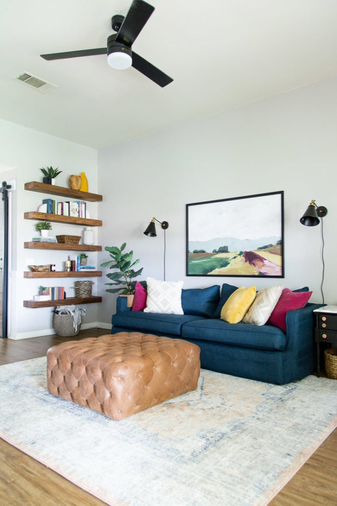 living room with a blue sofa, leather ottoman, and floating open shelving
