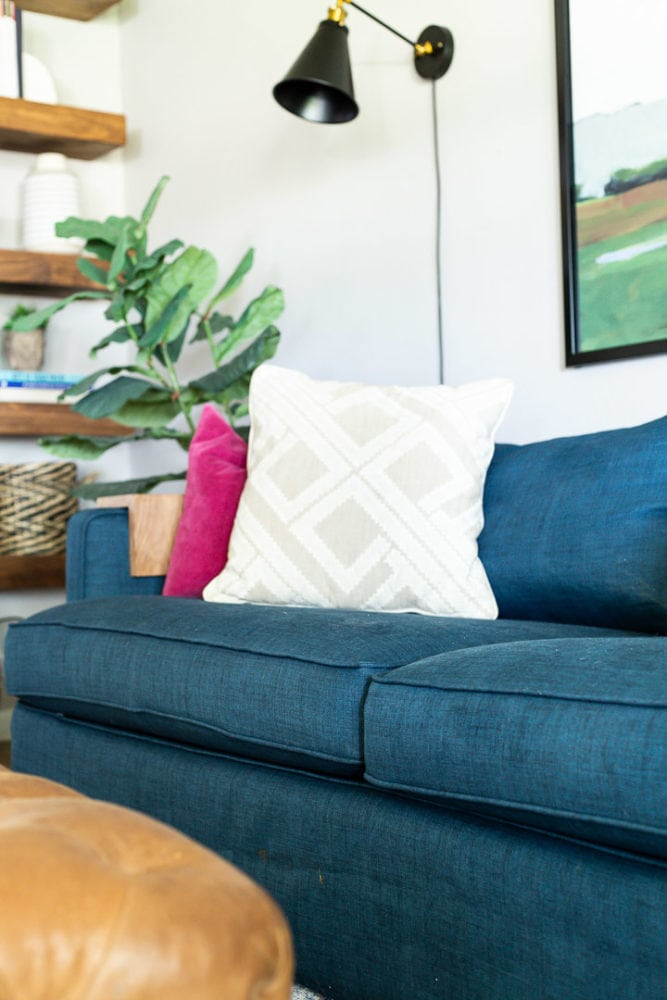 Close shot of a living room sofa with a Comfort Works slipcover on it and colorful throw pillows