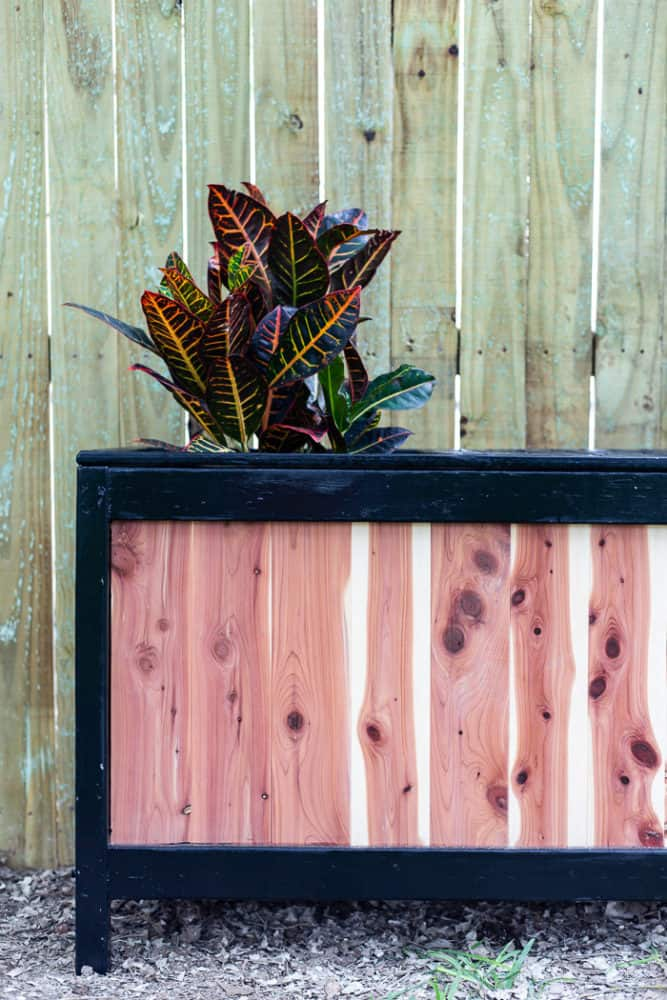 close up of a cedar planter with a bench built in