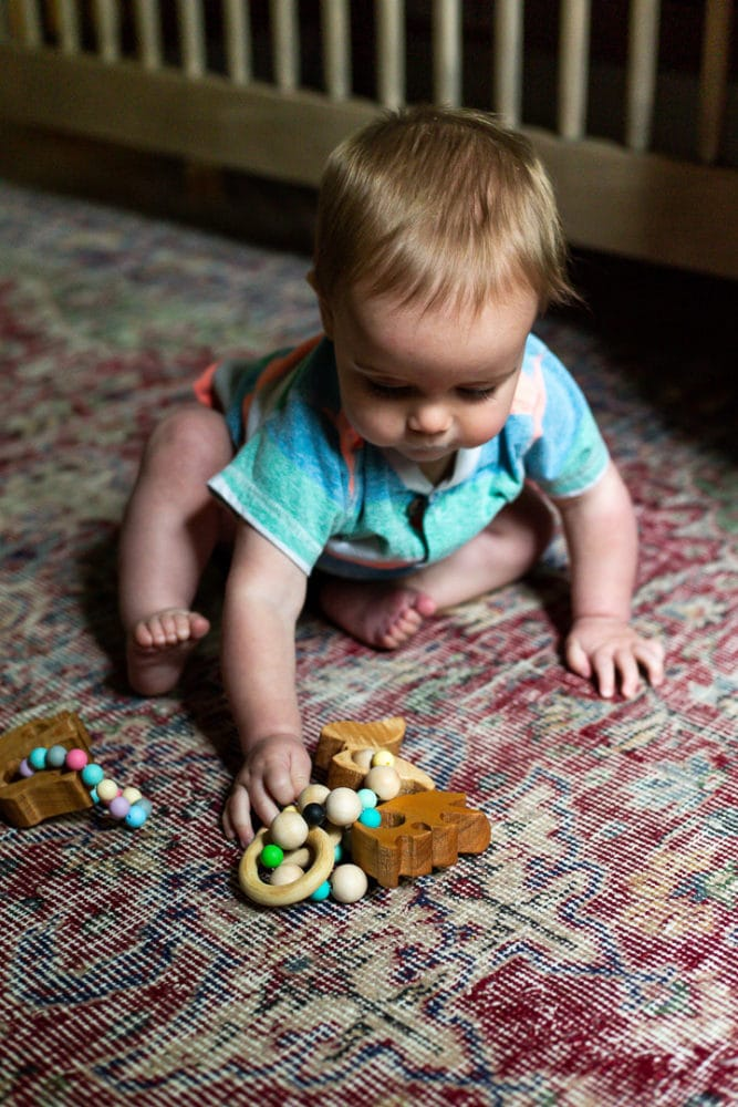 baby playing with wooden animal teethers