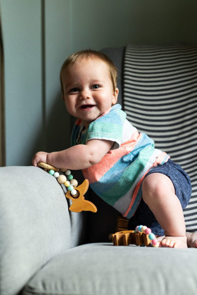 Smiling baby holding a teething toy