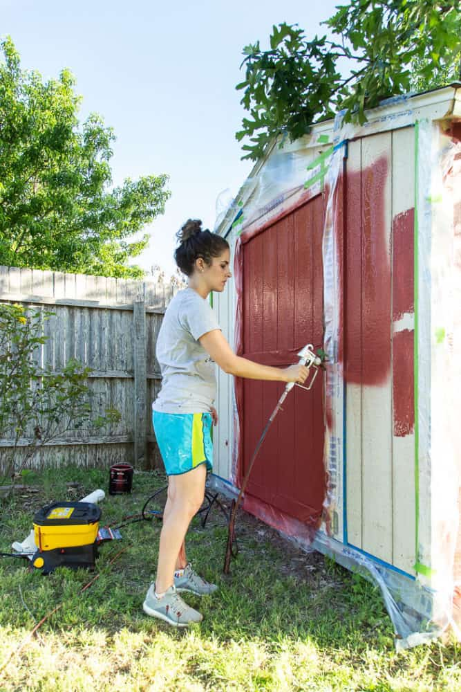 woman painting an outdoor shed