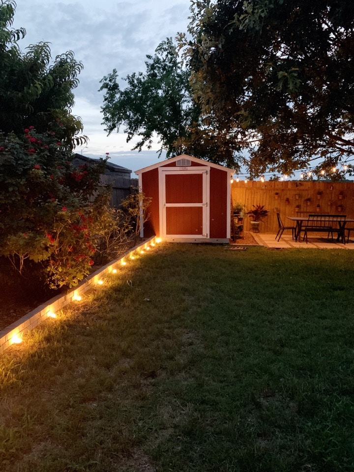 backyard lit up at night with landscape lighting