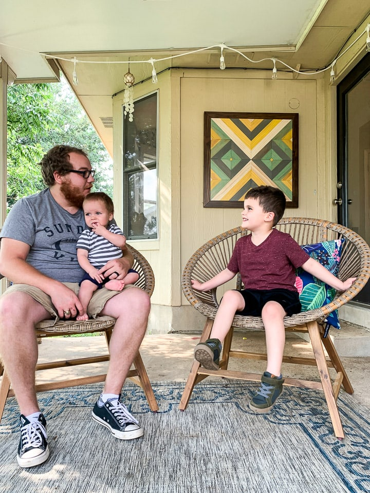 dad talking to two young sons on outdoor patio