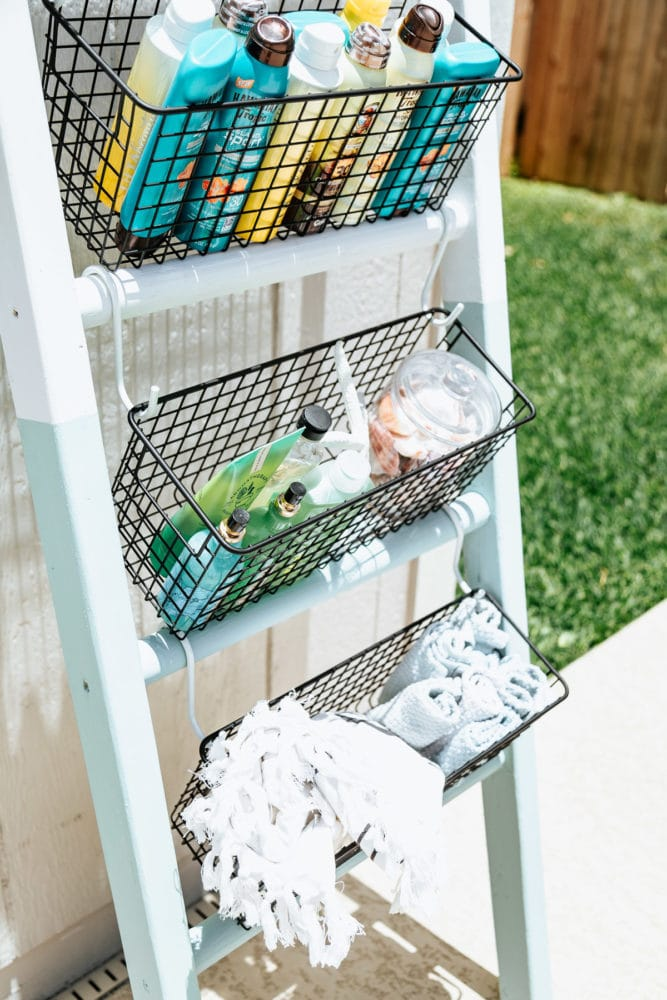 outdoor ladder holding pool supplies and sunscreen